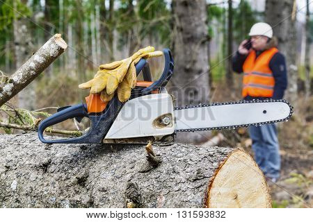 Chainsaw with gloves in background lumberjack talking on smart phone