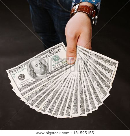 A man holding a fan of dollar banknotes. Shows on camera for money