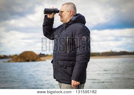 Man with binoculars at the lake .