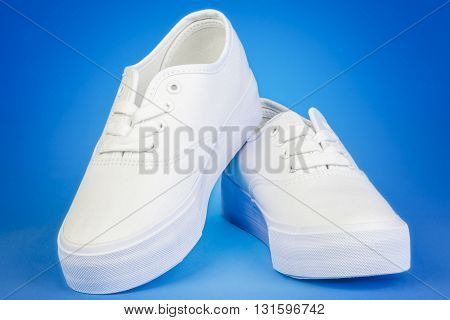 White Flatform Plimsolls on blue background .