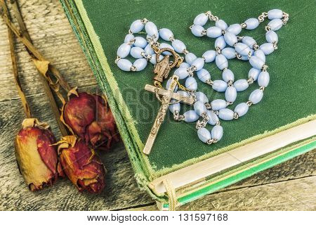 Rosary, bible and dried roses on the table