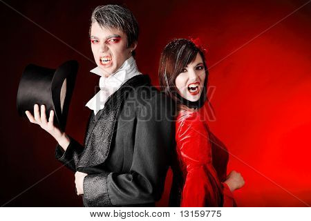 Portrait of a beautiful couple in medieval costumes with vampire style make-up. Shot in a studio.