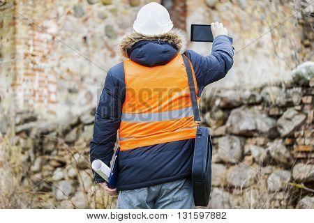 Building inspectors with tablet PC at old ruins