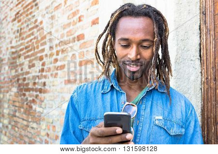 African american young man using mobile smart phone - Hipster guy model with modern smartphone - Male trendy person with cellphone and dreadlocks hairstyle - Concept of integration and new technology