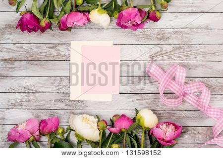 White and pink peonies flowers with pink ribbon and a blank card on the white painted wooden planks. Place for text. Square image. Top view.