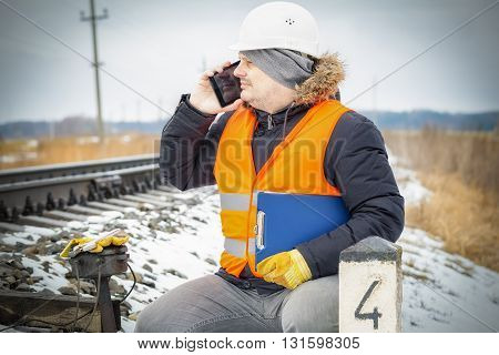 Railway employee talking on smart phone near the signal relays