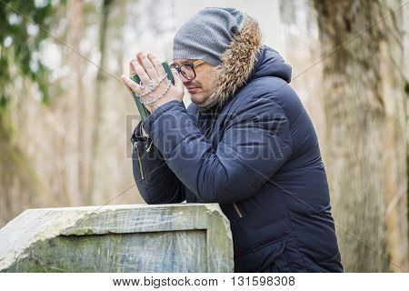 Man with Bible and Rosary praying near pedestal
