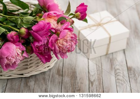 Beautiful flowers peonies in basket with gift box on the light wooden background.