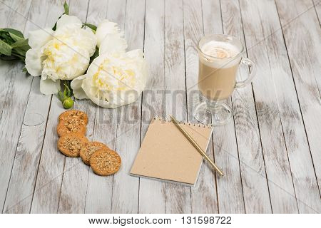 Notebook with a pencil next to glass of cappuccino and cookies on the white wooden background. Place for text.