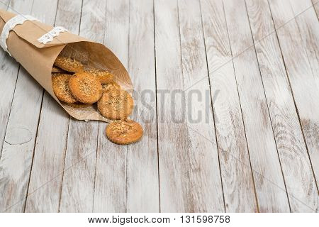 Cookies in paper bag on white the wooden background. Place for text.