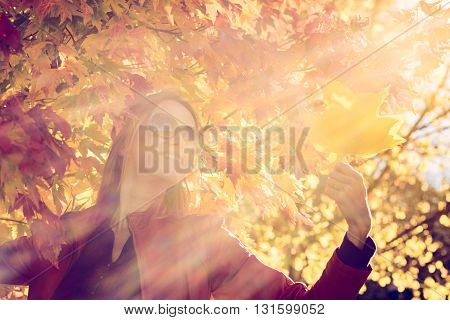 Cheerful woman with autumn leaves in her hand in autumn park. Lens flare effect is natural color-toning effect was applied.