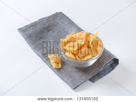 bowl of potato chips with bacon flavor on blue napkin