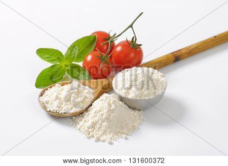 wheat flour on wooden spoon and in metal bowl, ripe tomatoes and fresh basil on white background