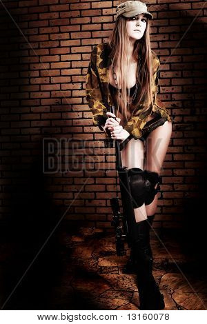 Shot of a sexy woman in military uniform posing against brick background.