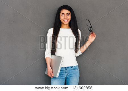 Young and successful. Attractive young African woman holding laptop and looking at camera with smile while standing against grey background