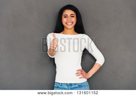 Good job! Attractive young African woman showing her thumb up and looking at camera with smile while standing against grey background