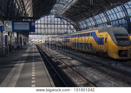 Amsterdam,the netherlands -16 February 2016: Built in 1885, the beautiful station of Amsterdam and just arrived yellow train of the Dutch railway