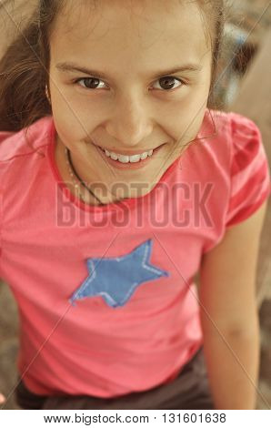 smiling young girl in a pink shirt in summer