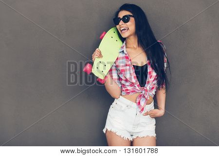 Ready to fun. Beautiful young mixed race woman carrying skateboard on shoulder and looking away with smile while standing against grey background