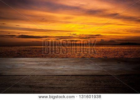 Wooden deck extending into the sea on sunset