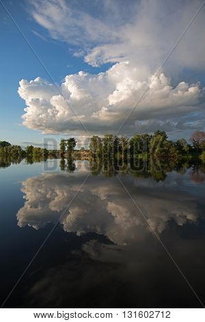 Beautiful white clouds and green trees range are reflected in water.