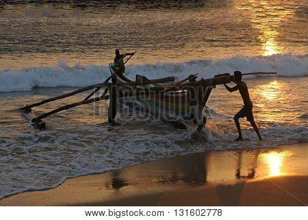 Wood fish boat starts from ocean beach. Scene at sunset. Only people silhouettes are seen.