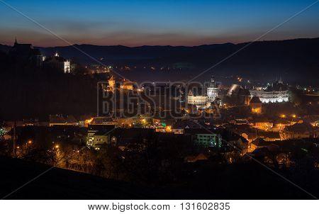 Illuminated Sighisoara town. Sunrise beginning in background.