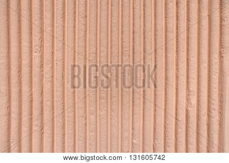 Apricot-colored facade with relief in vertical striped pattern in close-up