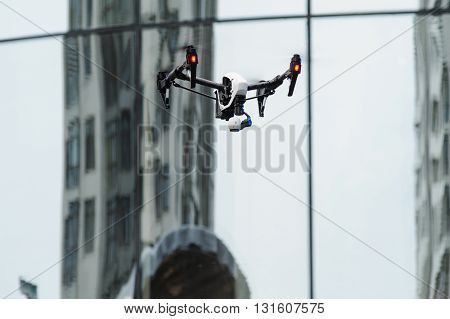 White quadrocopter drone with camera flying near house with glass windows