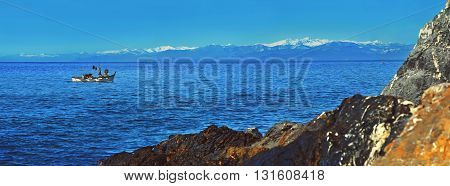Fishing boat at the Mediterranean sea with snow mountains background