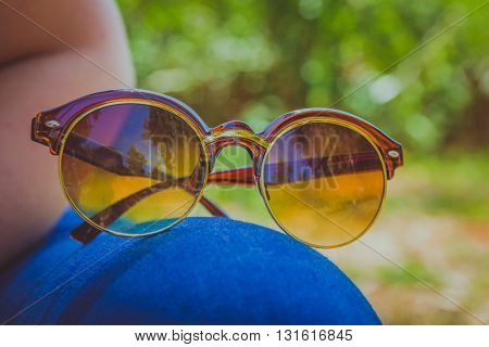 Brown sunglasses lying on the thighs of a woman who wears blue jeans and sitting outside on the grass.