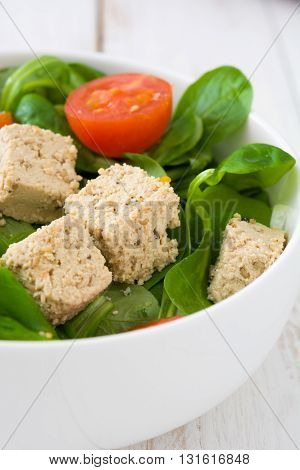 Vegan tofu salad with tomatoes and lamb's lettuce on white wood