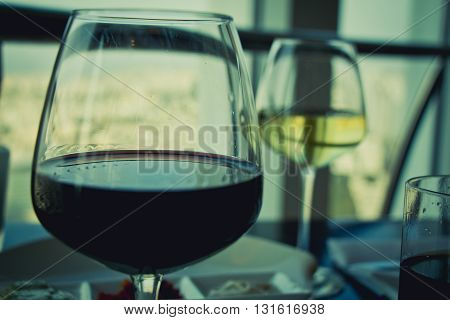 Close up on glasses with red and white wine on white table.