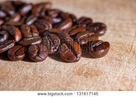 Close up picture of coffee beans on a light colored wooden cutting board