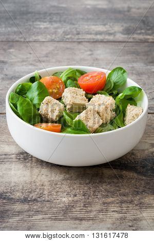 Vegan tofu salad with tomatoes and lamb's lettuce on rustic wood
