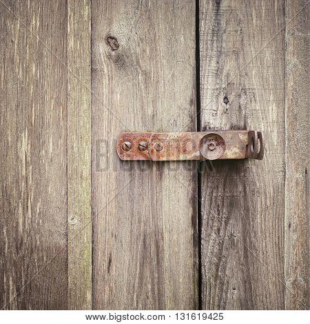 wooden door with a rusty metal lock