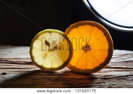 Slices Of Orange And Lemon On Rough Wooden Surface
