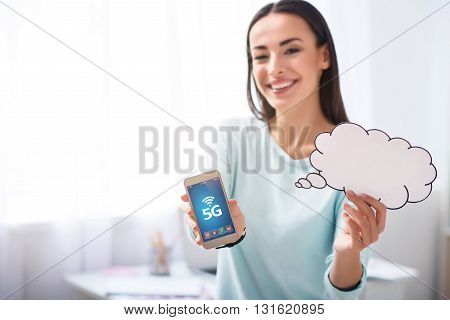 Connect the world. Pleasant delighted smiling woman holding cell phone and expressing gladness while standing in the office