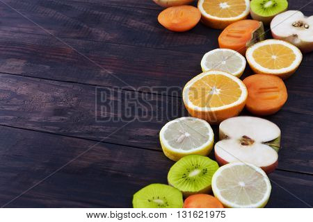 Slices Of Healthy Fruits Framing Rustic Wood With Copy Space
