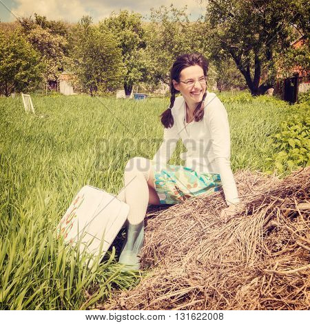 Portrait of a happy hipster girl with vintage painted suitcase sitting on a green meadow. Concept-expectation traveling. Toned image.