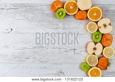 Slices Of Healthy Fruits On White Rustic Wooden Table