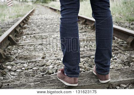 Close-Up Of Man's Feet Standing Between Railway Tracks