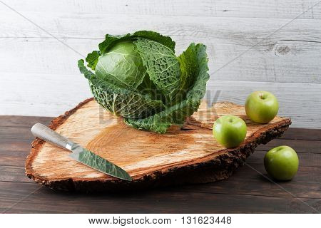 Whole Cabbage And Apples On Rough Wooden Chopping Board