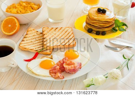 Covered table with breakfast with eggs and bakon