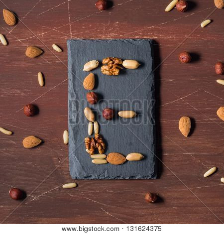 Vitamin E concept with different nuts - almonds, hazelnuts, walnuts, pine nuts on dark wooden background. top view image, square size