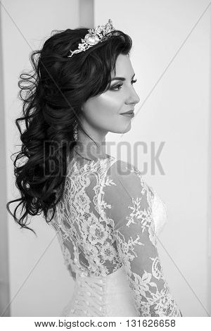 Happy beautiful bride smiling. Close portrait of a woman in a wedding dress. Natural light from the windows. Wedding hair and makeup.