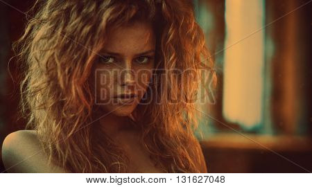 Young woman with red hair indoors portrait. Vintage film style soft warm colors.