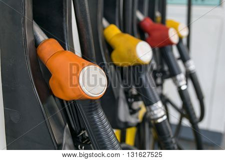 Pump nozzles at the gas station. Shallow depth of field with focus on the first nozzle. Selective focus
