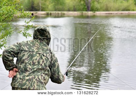 Fisherman with a fishing rod in anticipation of a bite a large trophy in Siberia