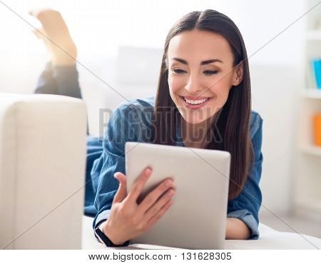 Relax at home. Pleasant cheerful beautiful smiling woman lying on the couch and using tablet while resting